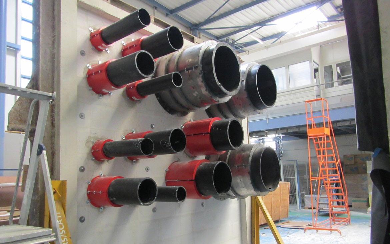 Prüfaubau einer Massivwand mit diversen KBS® Brandschutzmanschetten von KBS® Pipe Seal M 75 bis KBS® Pipe Seal M 630